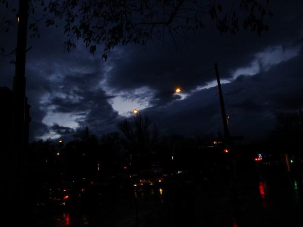 décors urbain à la tombée de la nuit sous la pluie avec des trouées de lumière dans le ciel