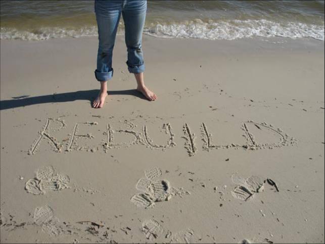 le mot rebuild écrit dans le sable