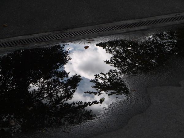 ciel se reflétant dans une petite flaque sur du goudron