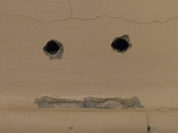 deux trous et une marque dans un mur pour faire un visage