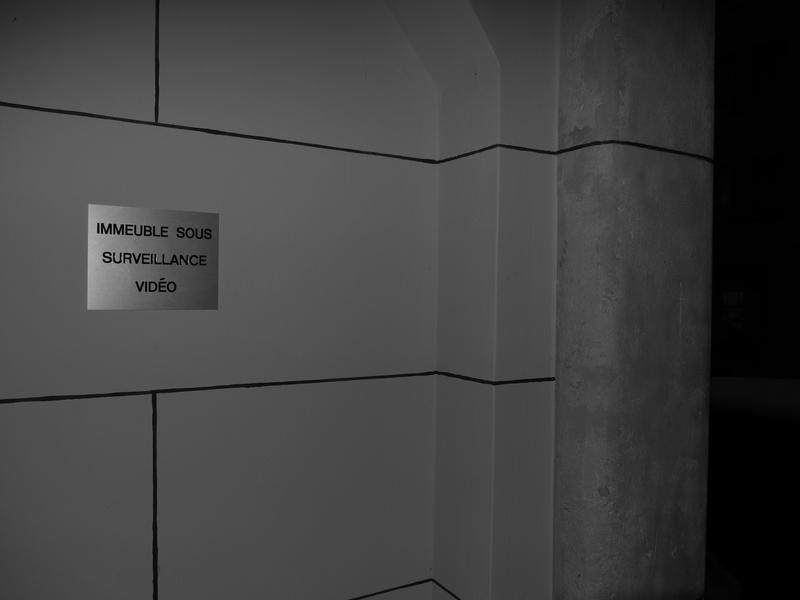 """Plaque à l'entrée d'un immeuble, photographiée de nuit au flash, sur laquelle il est écrit : """"Immeuble sous surveillance vidéo""""."""