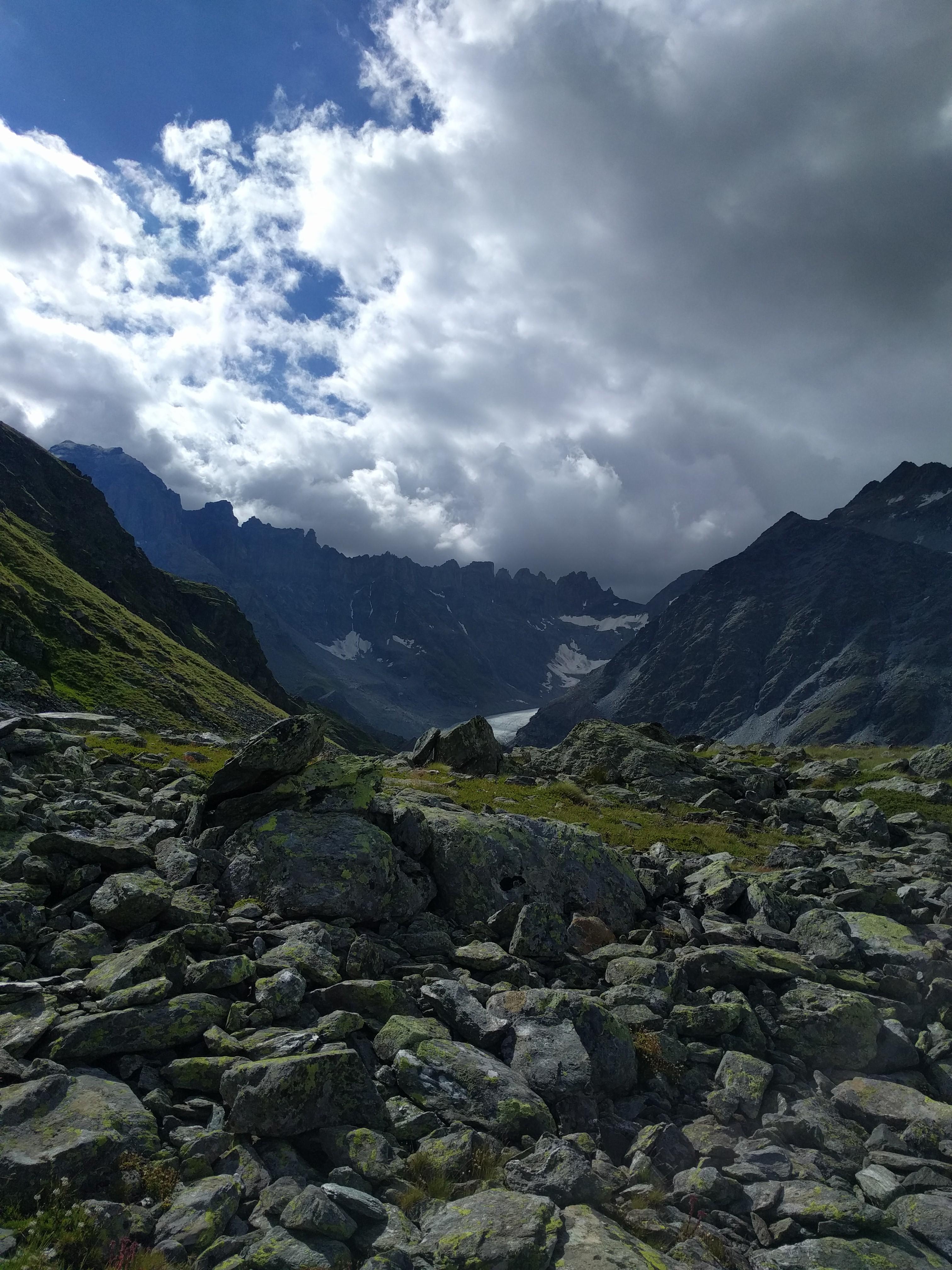 Pierres, cirque de montagnes et ciel nuageux