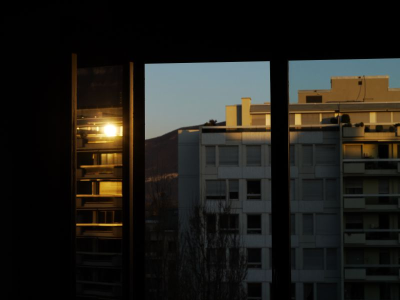 reflet d'un reflet de coucher de soleil, par le jeu des vitres ouvertes et fermées