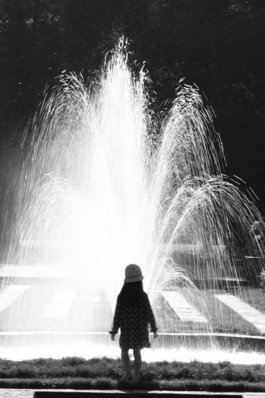 fillette de dos devant une fontaine, pause longue, noir-blanc