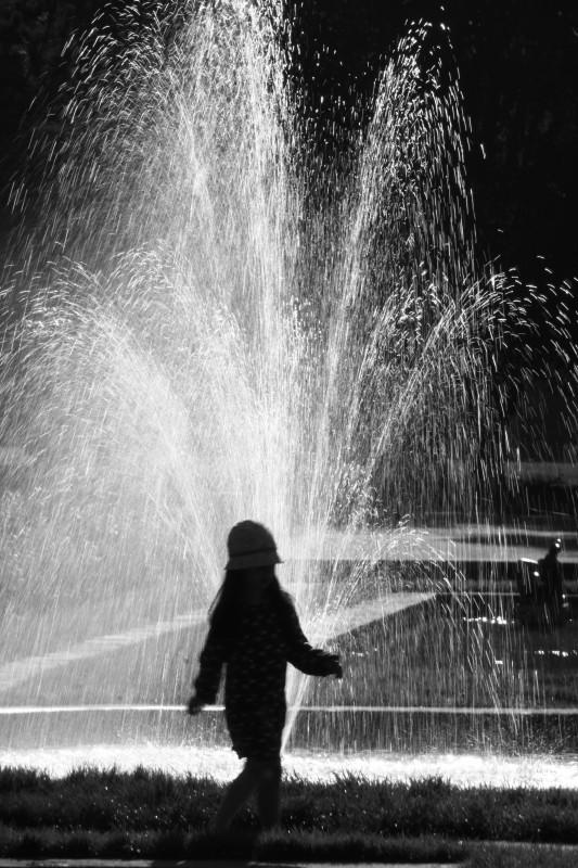 fillette passant devant une fontaine, noir-blanc