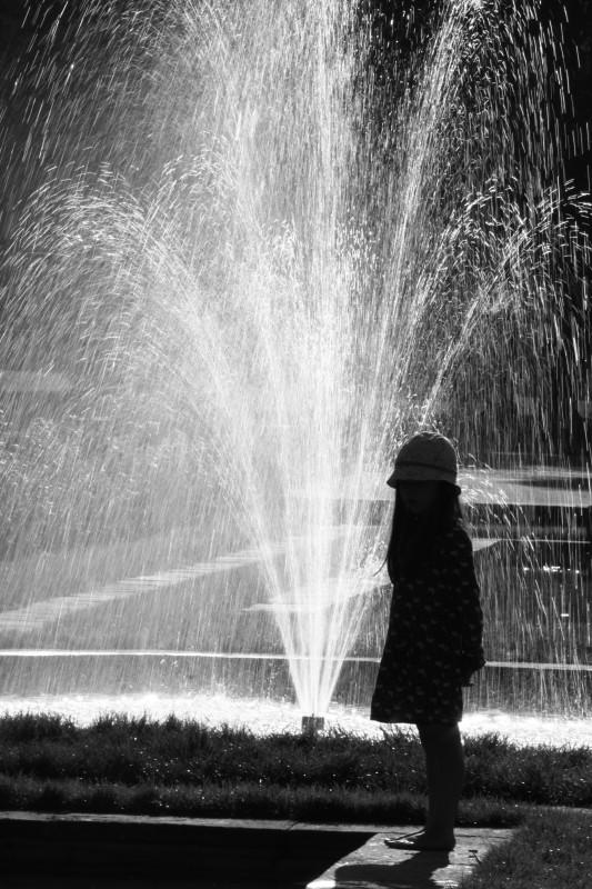 fillette devant une fontaine sur la gauche de l'image, noir-blanc