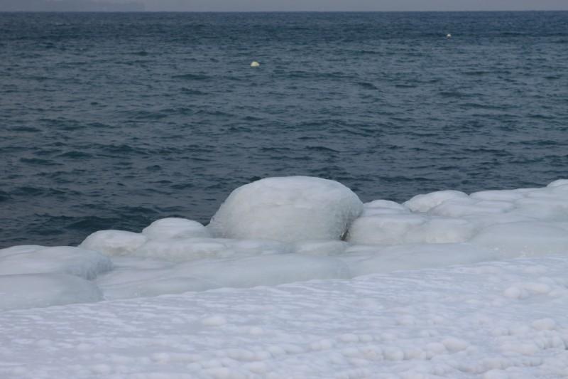 pierres longeant le bord du lac Léman gelées, trois bandes de couleurs, horizon, eau, gel