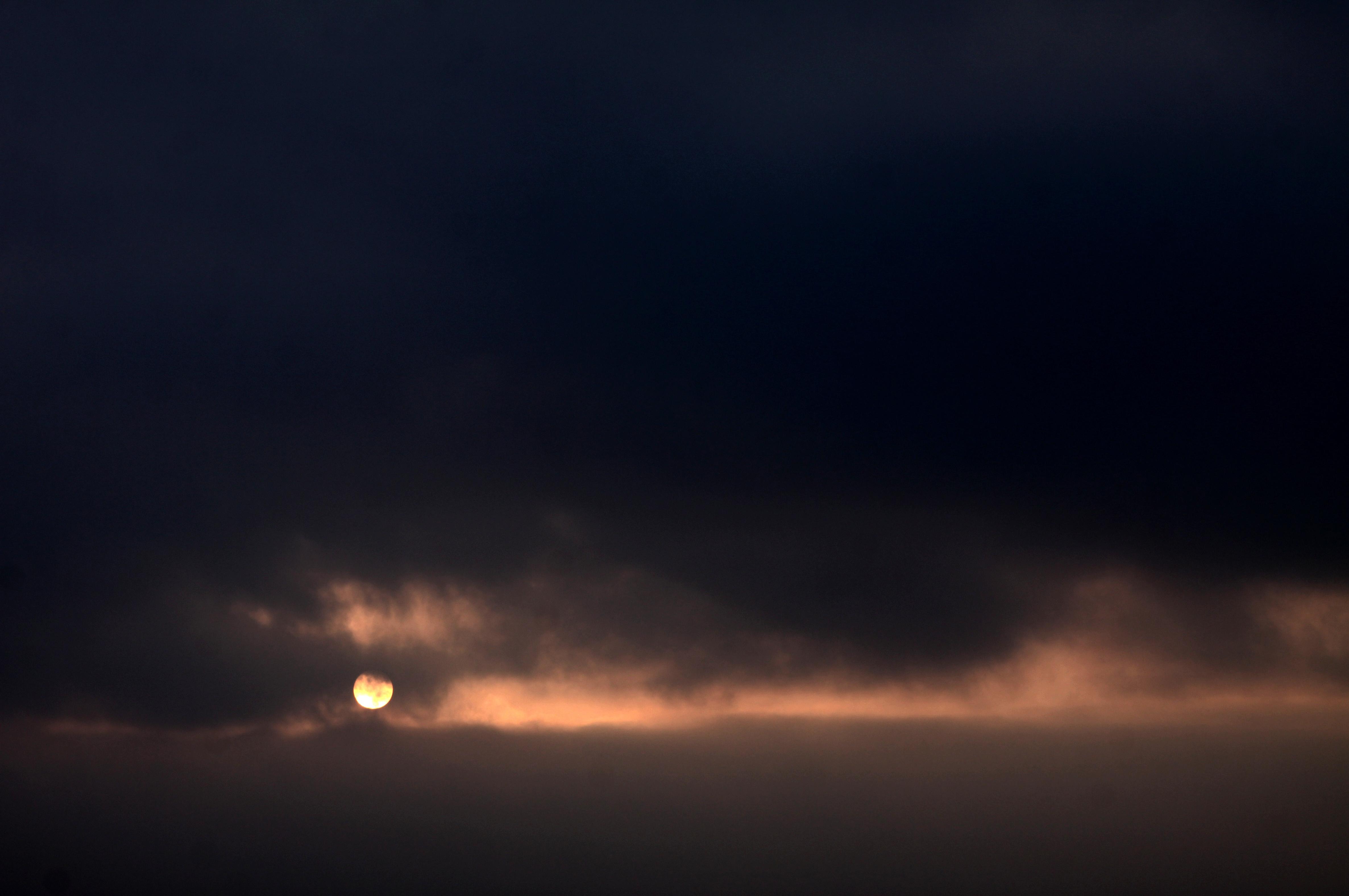 soleil rond derrière les nuages, ligne lumineuse entre les nuages