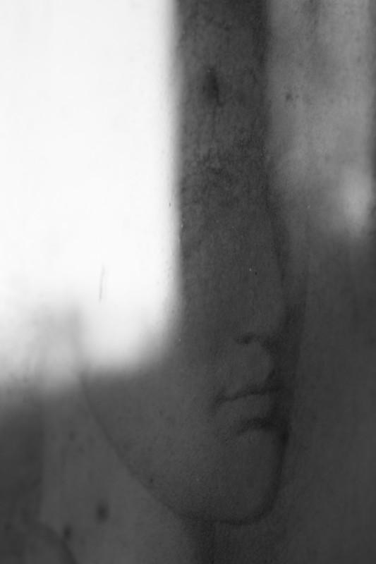 peinture d'un visage de femme avec le reflet de la lumière sur la vitre du cadre, noir-blanc