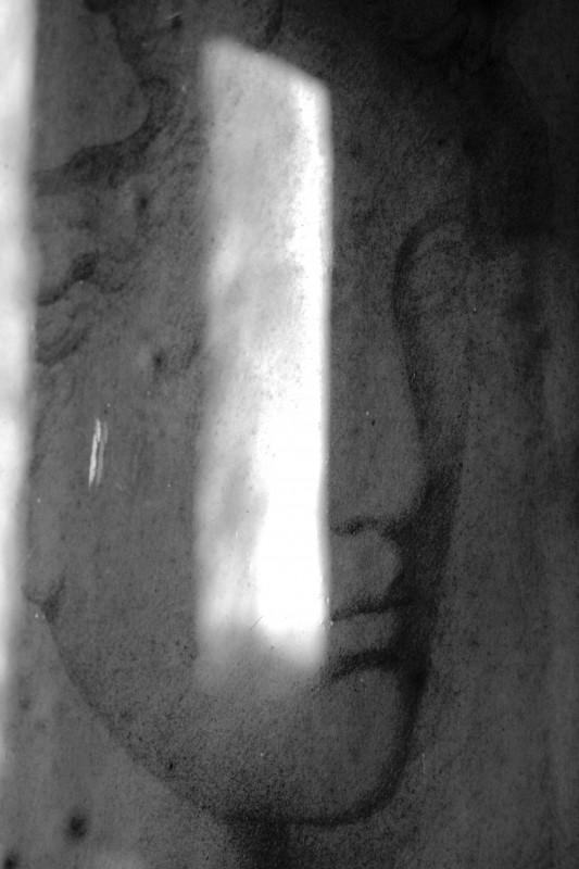 portrait d'une femme sous vitre, noir-blanc, avec reflet de la lumière sur la vitre