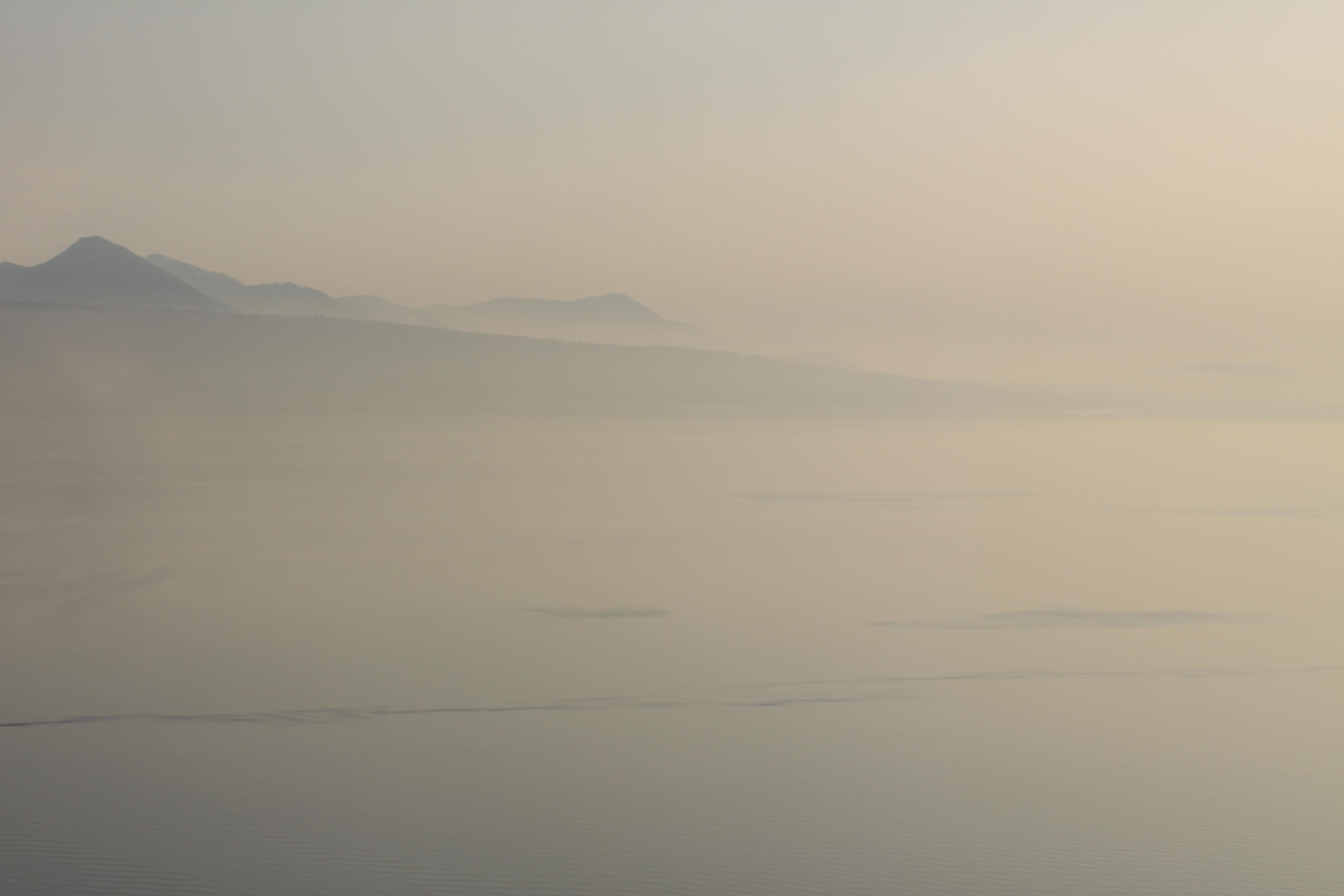 paysage d'une étendue d'eau en premier plan avec montagnes en arrière-plan, brume au-dessus du lac, Lac Léman
