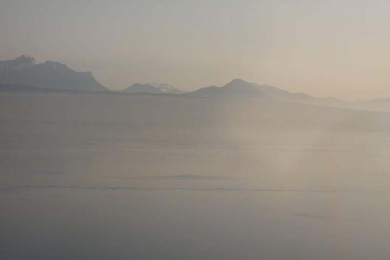 paysage , étendue d'eau, lac Léman en premier plan et montagnes en arrière-plan, bande de brouillard