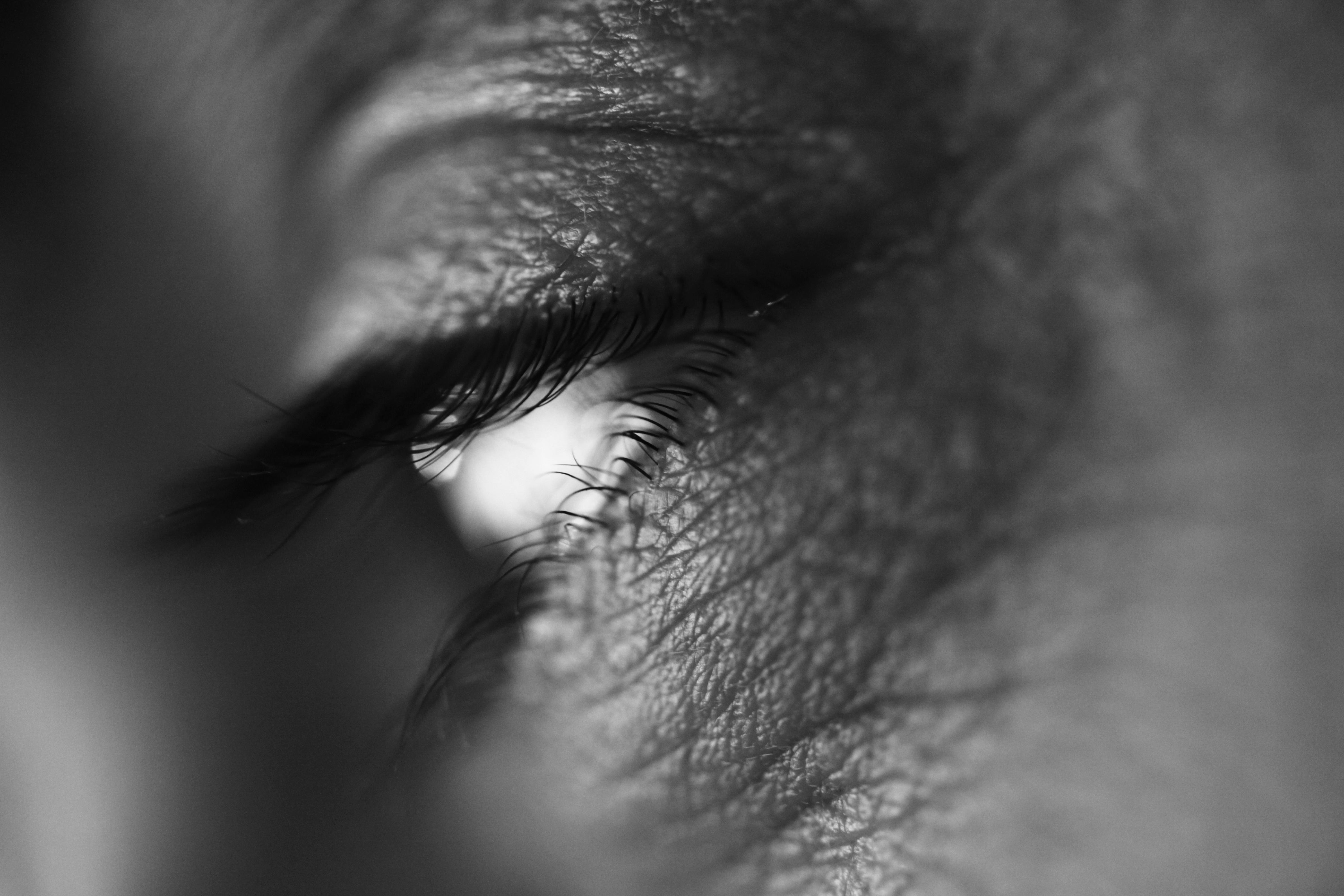 photo macro d'un oeil dont la pupille semble blanche à cause d'un reflet, noir-blanc