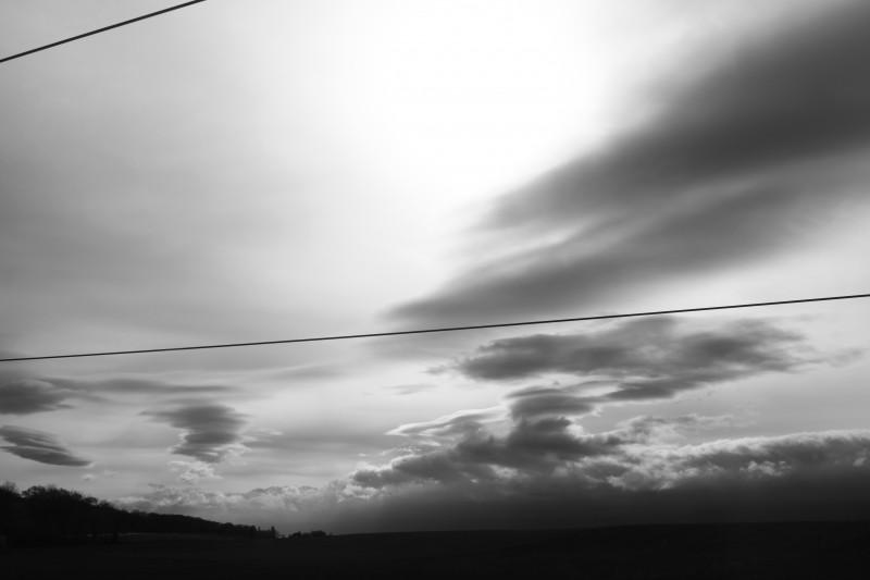 paysage en noir blanc, ciel nuageux, fils de trains barrant l'image