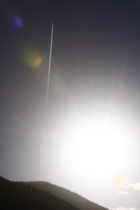 montagne en contre-jour avec soleil à droite de l'image et trace d'avion dans le ciel 2