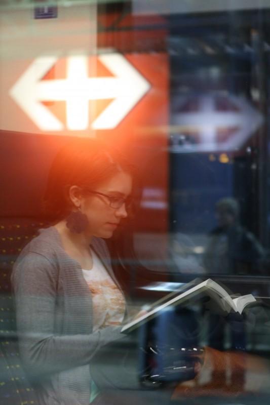 reflet dans la vitre d'un train, jeune femme lisant un livre