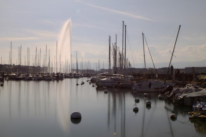 jet d'eau pause longue de jour, reflet sur le lac et bateaux sur onde lisse