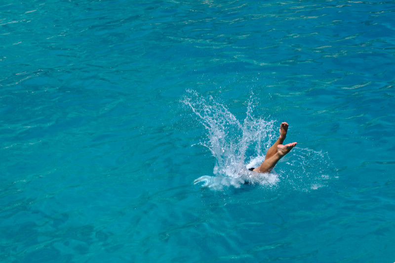 plongeon d'un homme dans l'eau turquoise de Sardaigne