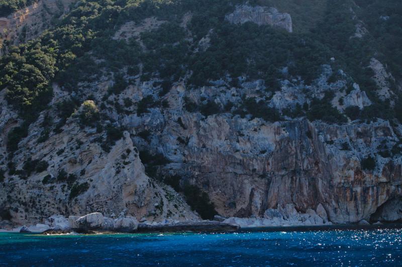 vue d'une falaise au bord de la mer, en Sardaigne, avec eau turquoise et scintillante de la mer